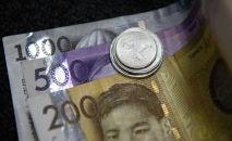 Монеты на сомовой купюре. Иллюстративное фото