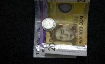 Сомовые купюры и монеты. Иллюстративное фото