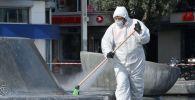 Сотрудник санитарной службы проводит обработку улиц в Стамбуле.