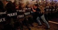 Житель города толкает полицейских во время антиправительственного протеста в Бангкоке (Таиланд)