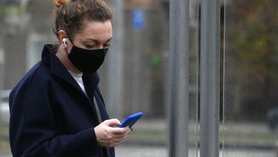 Девушка в защитной маске с телефоном в руках