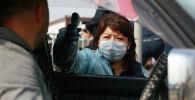 Алматыдагы блокпостто айдоочулардын температурасын текшерүү. Архивдик сүрөт