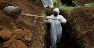 Мужчина в СИЗ копает могилу для умершего от COVID-19. Архивное фото