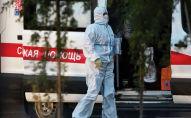 Медицинский работник и пациент с подозрением на коронавирус выходят из кареты скорой помощи