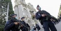 Сотрудники полиции стоят возле церкви Нотр-Дам, где произошло нападение на людей с ножом, Ницца, Франция. 29 октября 2020 года