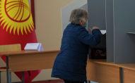 Женщина голосует на избирательном участке в ходе голосования на выборах седьмого созыва ЖК. Архивное фото