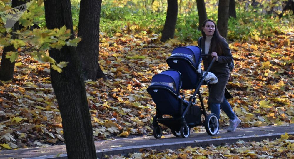 Паркта аял коляска менен бара жатат