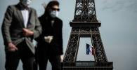 Мужчина и женщина в масках на фоне Эйфелевой башне в Париже. Архивное фото