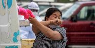 Женщина чихает, когда врач берет мазок из носа для тестирования на COVID-19. Архивное фото