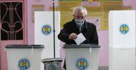 Мужчина голосует на всеобщих выборах президента Молдавии на одном из участков в Кишиневе.