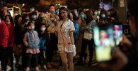 Девушка в костюме медсестры позирует перед толпой в ночь Хэллоуина (Китай)