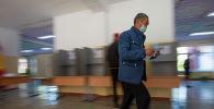 Мужчина несет бюллетень на избирательном участке. Архивное фото