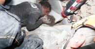 Спасатели вытаскивают ребенка из-под завала в результате землетрясения в Измире, Турция