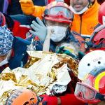 Трехлетняя выжившая Элиф Перинчек держит за большой палец спасателя, пока ее выносят из обрушившегося здания. Девочка провела под завалами 65 часов.