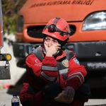 Девушка-спасатель отдыхает и ест бутерброд во время продолжающейся поисковой операции на месте обрушившегося здания