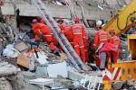 Спасатели разбирают завалы разрушенного из-за сильного землетрясение дома в городе Измир (Турция)