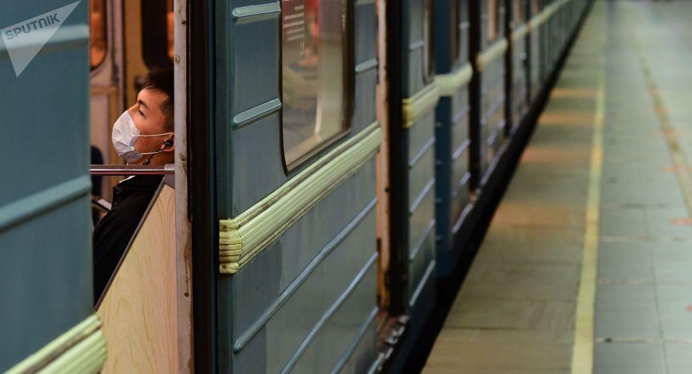 Поезд вагонундагы медициналык маскадагы жүргүнчү. Архив