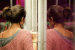 Девушка стоит у зеркала. Архивное фото