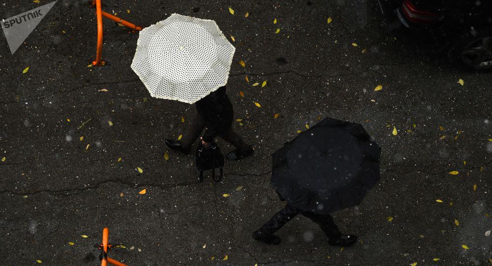 Прохожие во время дождя на улице. Архивное фото