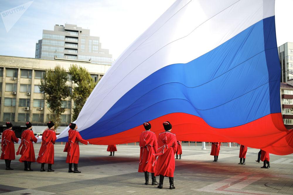 Кубандык казактар армиясынын ардактуу кароолу Улуттук биримдик күнүндө Краснодардын башкы аянтында Россиянын желегин көтөрүп жатат