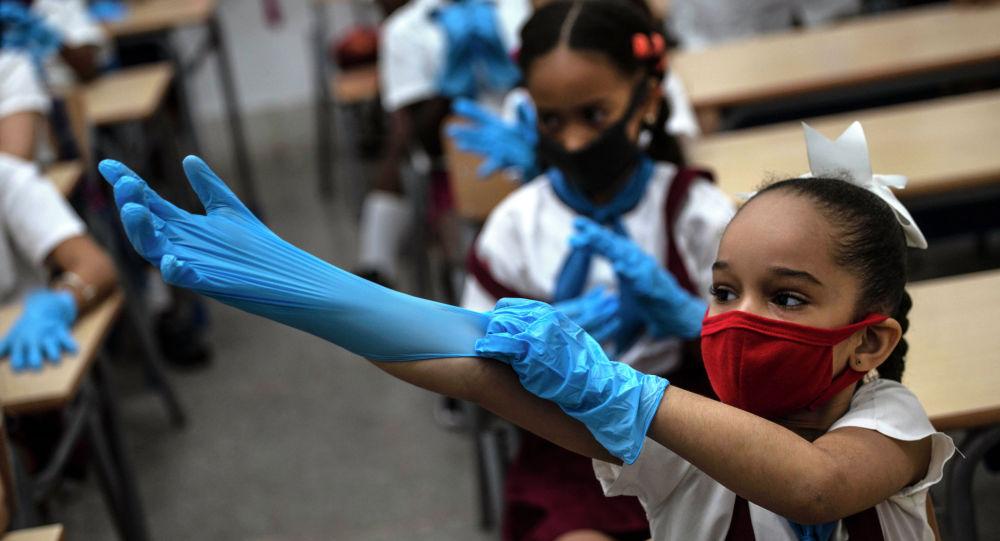 Школьница надевает перчатки в классе в Гаване. Архивное фото