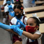 Гаванада (Куба) мектеп окуучусу класста коргонуучу кол кап кийип жатат