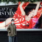 Лондон шаарында (Англия) карантин чаралары күчөгөндүктөн жабылган дүкөндүн алдынан өтүп бара жаткан адам