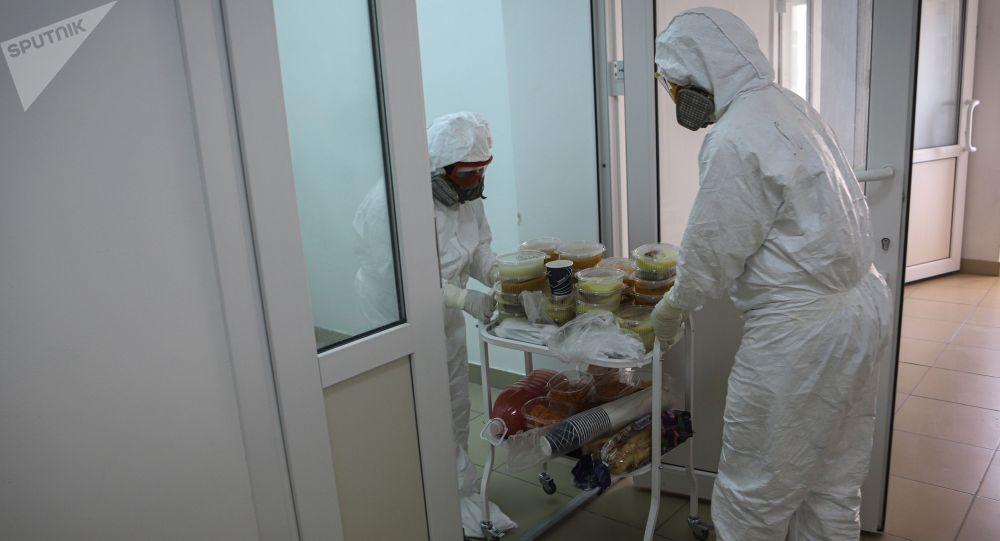 Медицинские работники во время доставки обеда для пациентов в одноразвоой посуде. Архивное фото