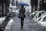 Девушка с зонтом идет по одной из улиц Бишкека во снегопада. Архивное фото