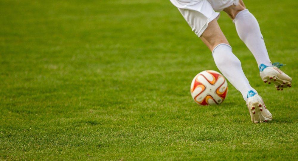 Футболчу топ менен матч учурунда. Иллюстративдик сүрөт