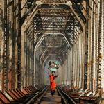 Мумбайлык аял темир жол менен баштыгын башына көтөрүп келе жатат