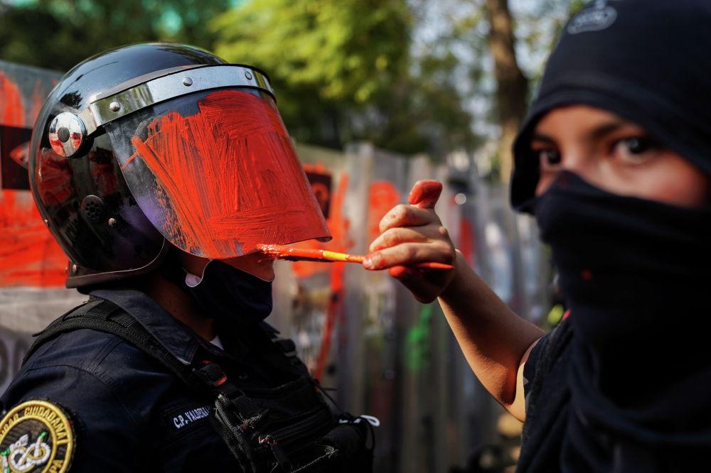 Гендердик теңсиздикке каршы нааразылыкка чыккан аялдын полициянын коргонуучу каражатын сырдап салган учуру. Мехико, Мексика