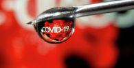 Слово COVID-19 отражена в капле на игле шприца на этой иллюстрации. 9 ноября 2020 года