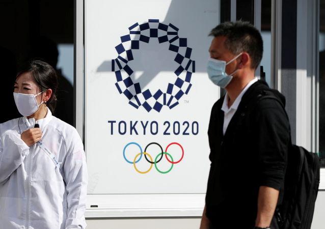 Токио олимпиадасынын логотибинин тушунда турган беткапчан адамдар. Архивдик сүрөт