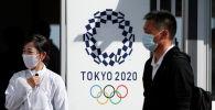 Люди в масках на фоне логотипа Олимпийских игр 2020. Архивное фото