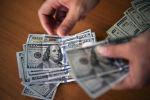 Мужчина, считающий доллары США. Архивное фото