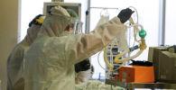 Врачи осматривают пациента с коронавирусом