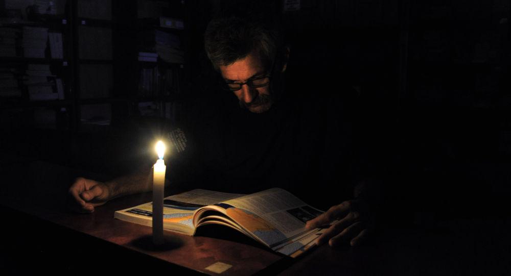Человек читает со свечой во время отключения электроэнергии. Архивное фото