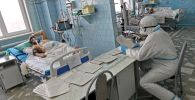 Медицинский работник и пациент в отделении интенсивной терапии ковид-госпиталя