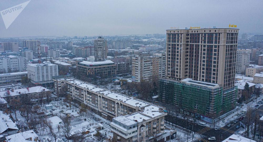 Вид на жилые дома на улице Киевская с высоты во время снегопада в Бишкеке