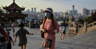 Девушка в медицинской маске посещает Башню желтого журавля в Ухане (Китай). Архивное фото