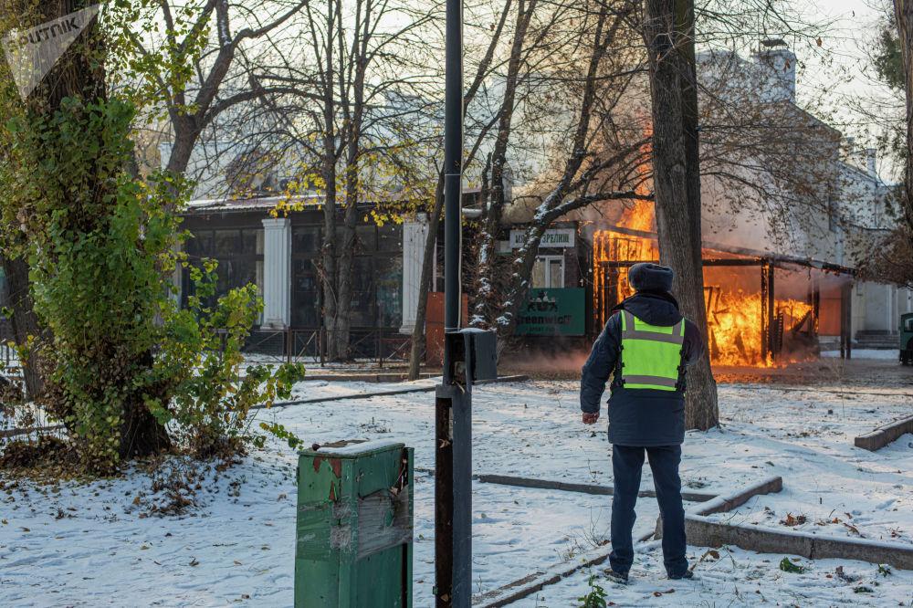 Сотрудник милиции во время пожара в кафе в центре Бишкека возле кинотеатра Ала-Тоо. 20 ноября 2020 года