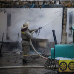 Сотрудник МЧС во время тушения пожара в кафе в центре Бишкека возле кинотеатра Ала-Тоо