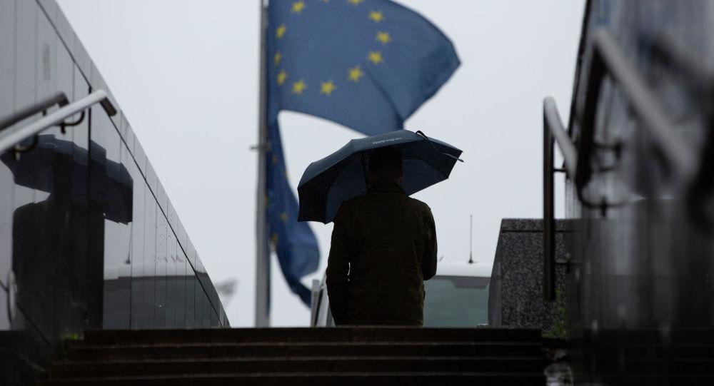 Киши Евробиримдиктин желектеринин жанында кол чатыр менен бара жтат. Архив