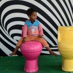 Мальчик в Нью-Дели сидит на унитазе во время кампании Туалеты — это красиво по случаю Всемирного дня туалета.  В индии проблема отсутствия туалетов стоит особенно остро.