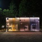 Мужчина у общественного туалета из стекла в мини-парке Yoyogi Hukamachi в Токио, Япония. Когда человек входит внутрь, стекла перестают быть прозрачными.