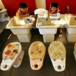Дети едят мороженое из миниатюрных туалетов в тематическом ресторане в Гаосюне, Тайвань