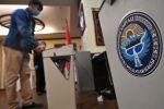Мужчина опускает бюллетень в урну для голосования. Архивное фото