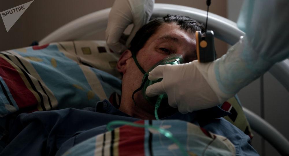Пациенту надевают кислородную маску в стационаре для больных COVID-19. Архивное фото