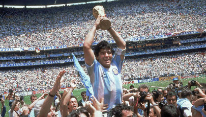 Диего Марадона из Аргентины празднует победу с кубком в финале чемпионата мира по футболу на стадионе Ацека в Мехико. Мексика 29 июня 1986 года